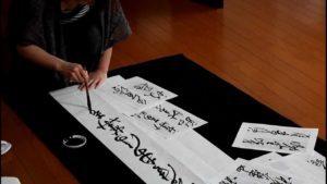 person writing in Japanese kanji