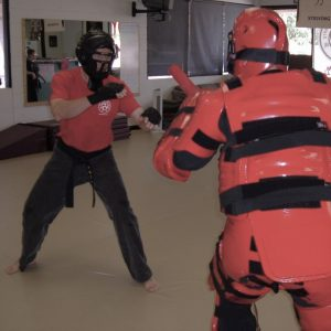 Black belt man faces an attacked wearing redman protective suit