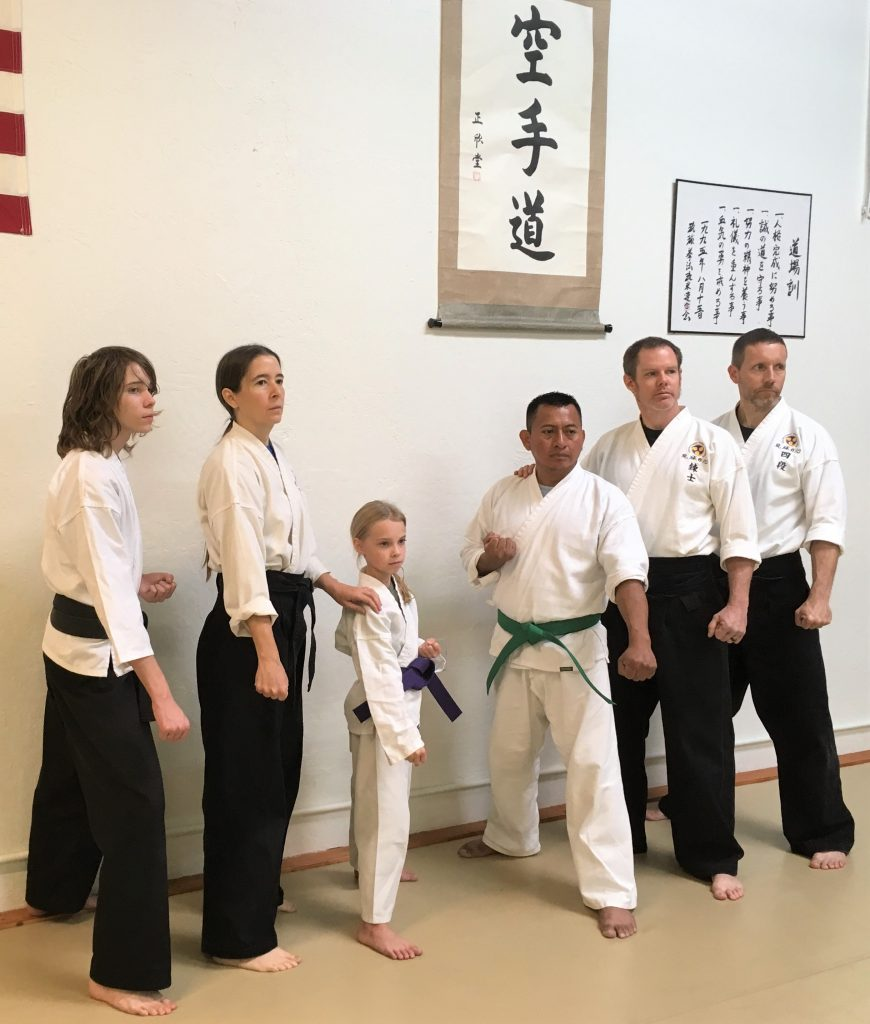 Karate students and instructors pose under karate-do banner