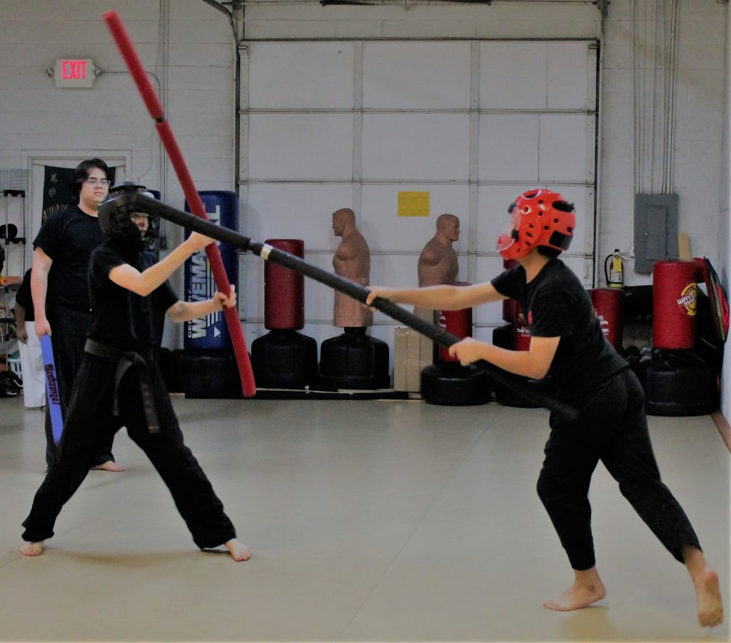 padded weapons sparring with a partner