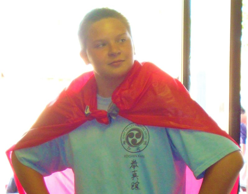 volunteer donning a cape while lending dojo support