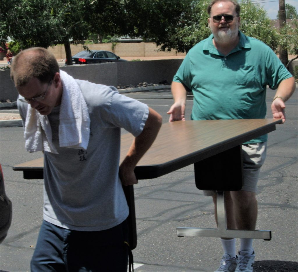 Karate dads carrying a table.