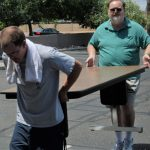 two karate dads carry a large table