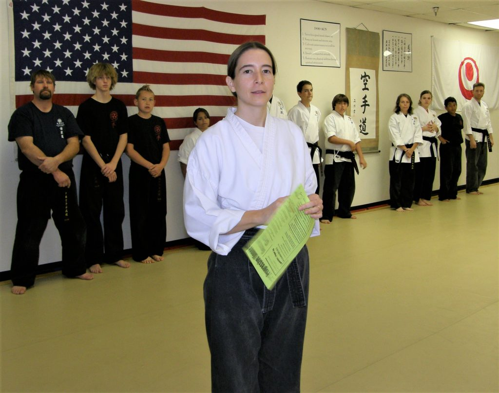 Karate teacher with black belt students in the background.