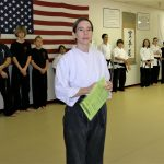 a karate teacher with black belt students in the background