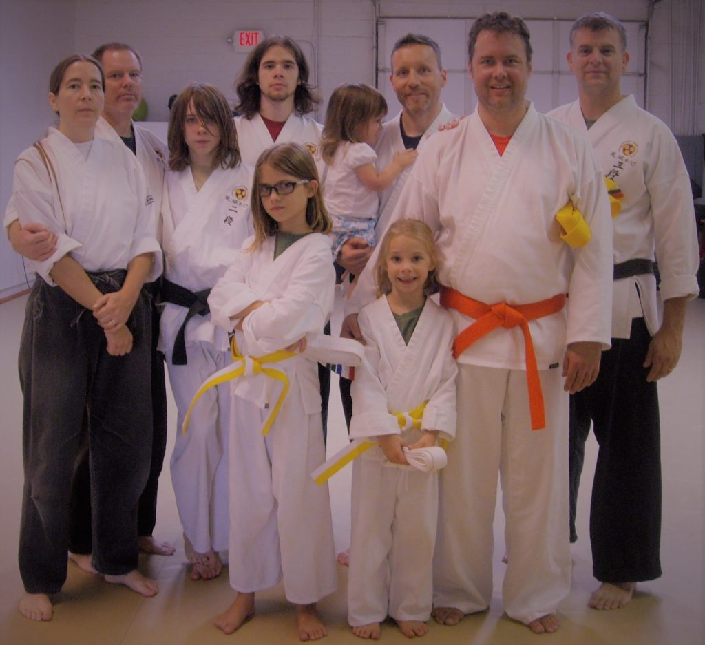 a happy group of karate practitioners of all ages and ranks, posing in uniforms