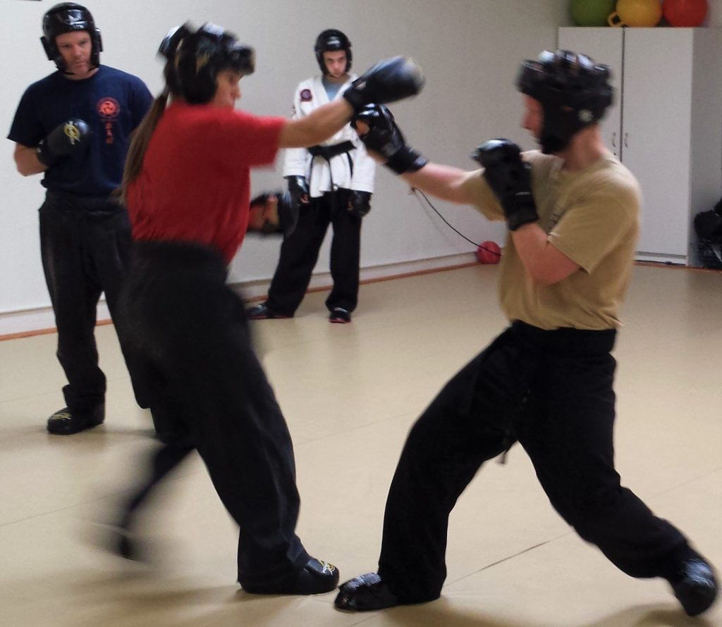 karate safety systems in sparring with partners wearing proper gear and black belt supervision