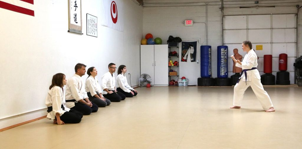 all in uniform, a teen karate student who studied karate for children performing a stance in front of black belts