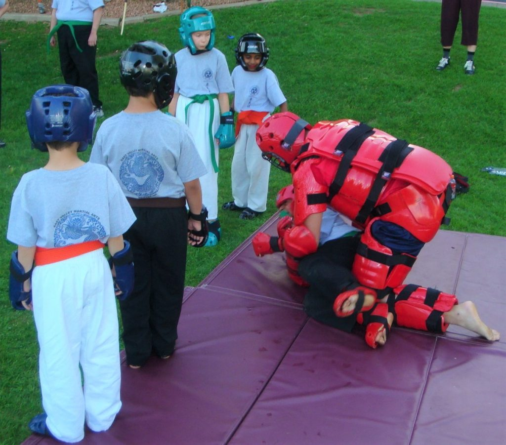 in an active karate for children activity, a kid is attacked by an adult in protective gear