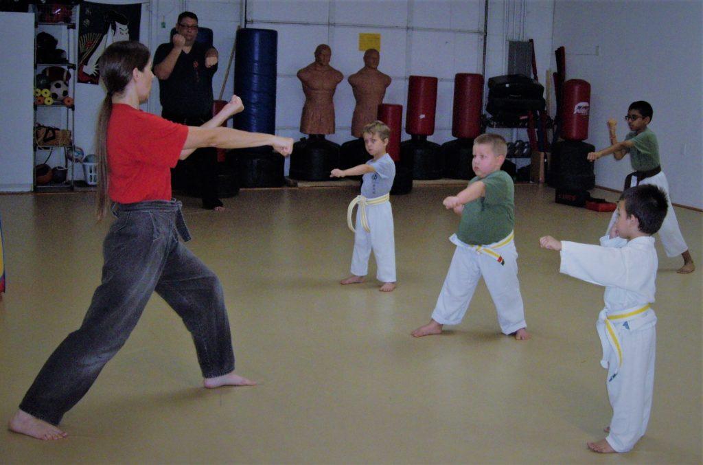 karate kids learning from black belt