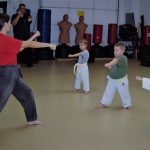 karate kids learning from black belt